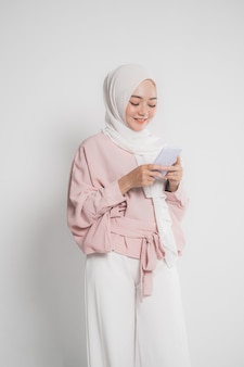 Красивая молодая мусульманская женщина улыбается во время текстового сообщения на мобильном телефоне, изолированном на белом изолированном фоне