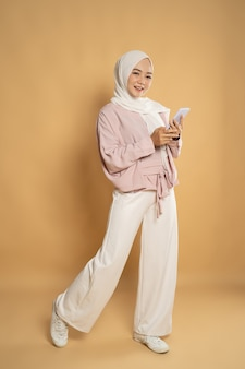 Красивая молодая мусульманская женщина улыбается во время текстового сообщения на мобильном телефоне