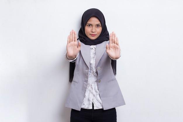 심각한 표정의 방어 제스처로 정지 신호를 하고 열린 손을 가진 아름다운 젊은 이슬람 여성