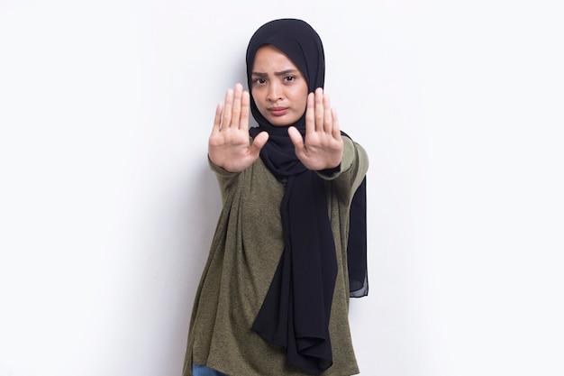 진지한 표정의 방어 제스처로 정지 신호를 하고 열린 손을 가진 아름다운 젊은 이슬람 여성