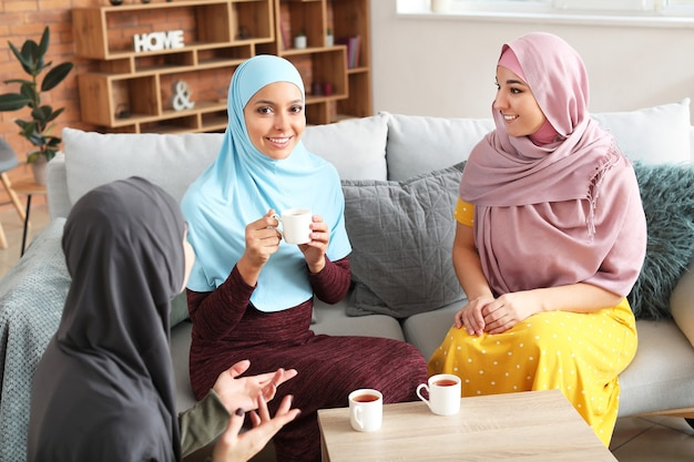 집에서 차를 마시는 아름 다운 젊은 무슬림 여성