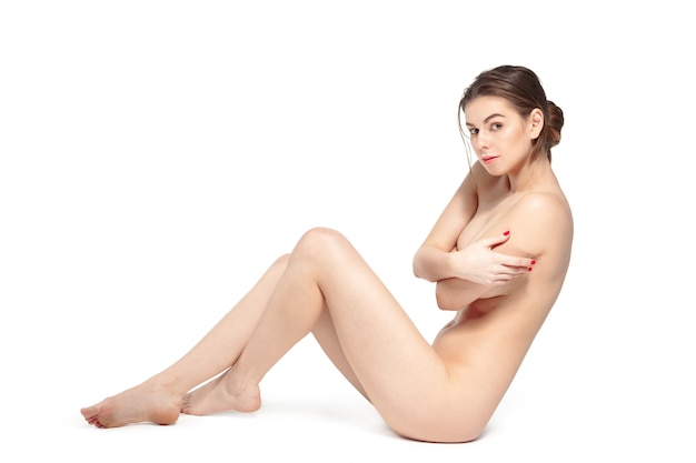Beautiful young naked brunette woman lying
