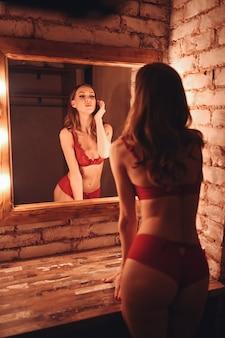 아름다운 젊은 자연의 아름다움 섹시한 여자가 반사를보고 빨간 레이스 속옷에 할리우드 스타일의 화장대 화장 거울에 포즈