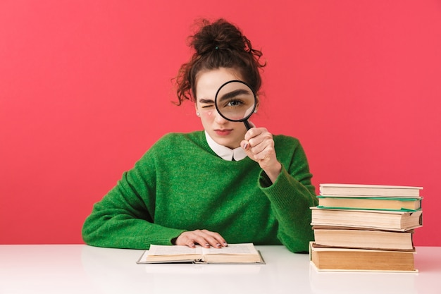 Beautiful young nerd student girl sitting at the table isolated, studying with books, holding magnifying glass