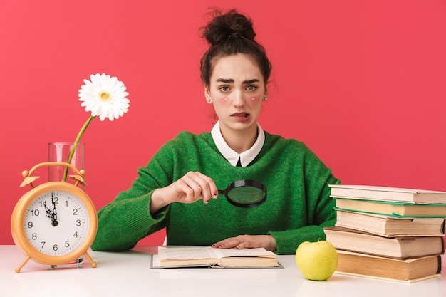 Beautiful young nerd student girl sitting at the table isolated, studying with books, magnifying glass