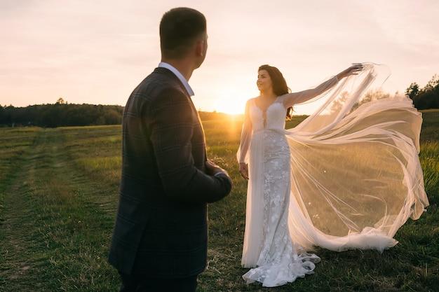 フィールドで日没時の美しい若い新婚カップル