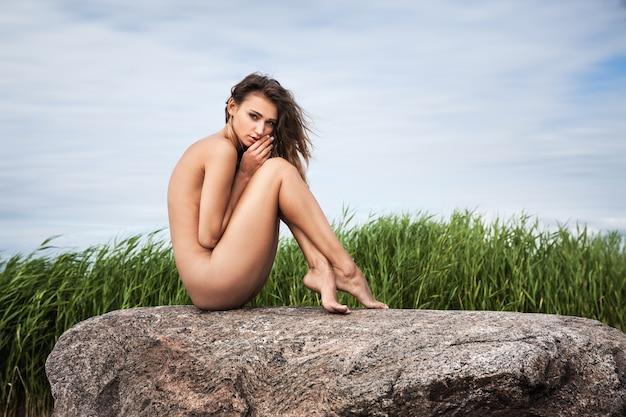 자연 배경에 대해 돌에 앉아 아름 다운 젊은 누드 여자