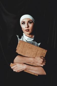 종교 검은 양복에 아름 다운 젊은 수녀는 성경을 보유하고 검정색 배경에 큰 책을 카메라에 포즈. 종교 개념.