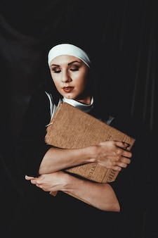 Beautiful young nun in religion black suit holds bible and posing on camera with big book on a black surface