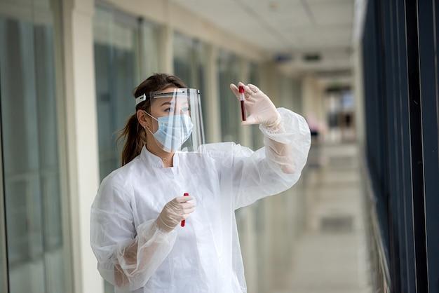 保護マスクとフェイスシールドとユニフォームを着た美しい若い看護師が、コロナウイルス感染について試験管内の血液サンプルを検査します。 covid19