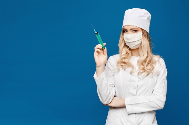 Beautiful young nurse in medical robe holding syringe. medical injection. pretty young woman doctor with a syringe. pharmacy and medicine concept