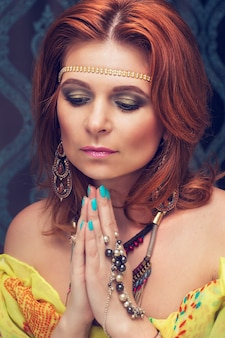 美しい若い東洋の女性は祈りの中で手を組んだ