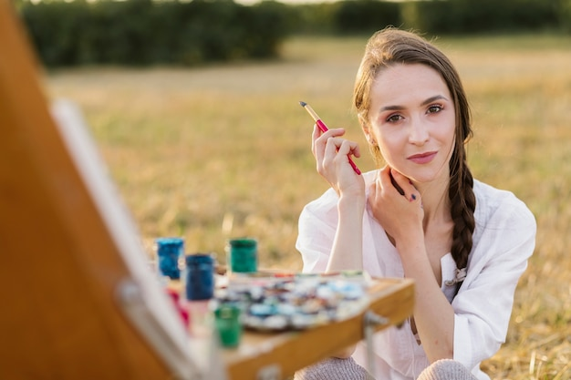Beautiful young painter looking at camera