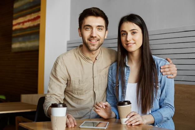 Beautiful young pair with dark hair in casual clothes smiles, drinking coffee and posing for photo in university article about perspective startup project.