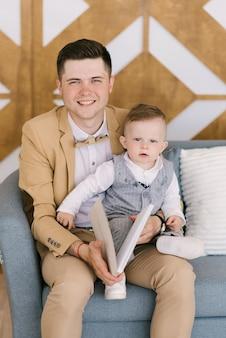 Красивый молодой родитель улыбается со своим годовалым ребенком дома