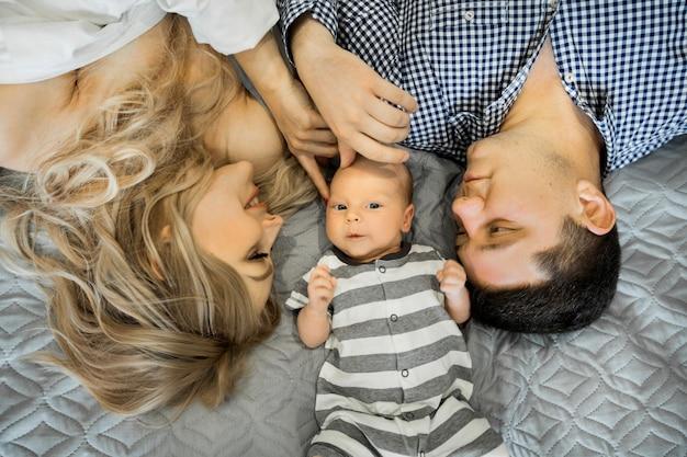 아름다운 젊은 부모 엄마와 아빠가 작은 아이들과 함께 침대에 누워있다