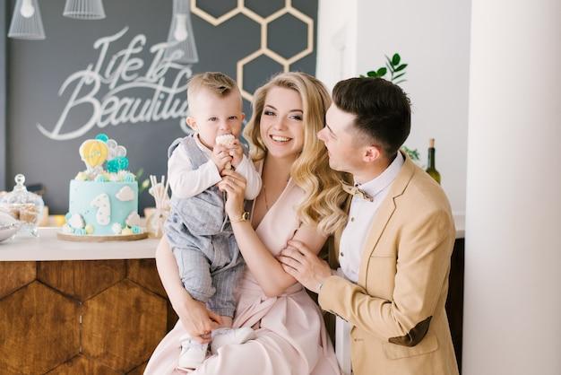 美しい若い親が1歳の子供と一緒に、パステルカラーの美しいインテリアで、お祝いの青いケーキを添えて、笑顔で家にいます。家族の一見。ハッピーバースデーパーティー