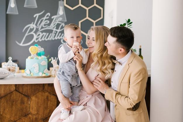 美しい若い親は、お祝いの青いケーキとパステルカラーの美しいインテリアで自宅で1歳の子供と一緒に笑顔します。家族の外観。ハッピーバースデーパーティー