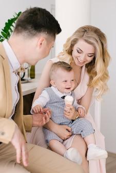 美しい若い親は自宅で1歳の子供と笑顔