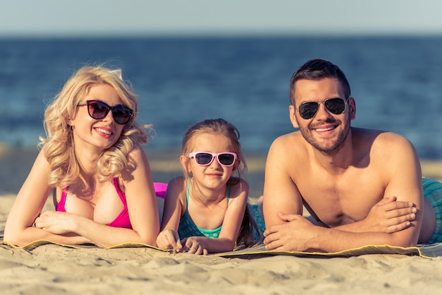Beautiful young parents and their daughter on beach.