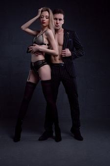 Beautiful young passionate couple embracing in a room with low light