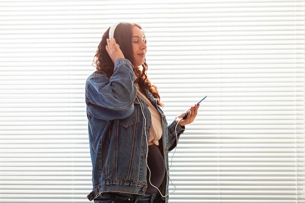 美しい若い平和な妊婦は音楽を聴きます