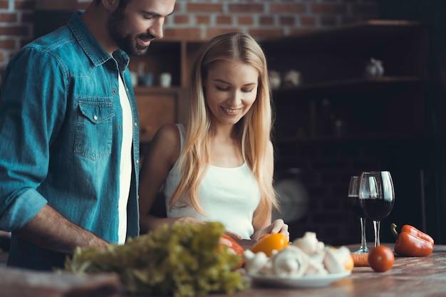 집에서 부엌에서 건강에 좋은 음식을 요리하는 동안 아름다운 젊은 사람들이 이야기하고 웃고 있습니다.