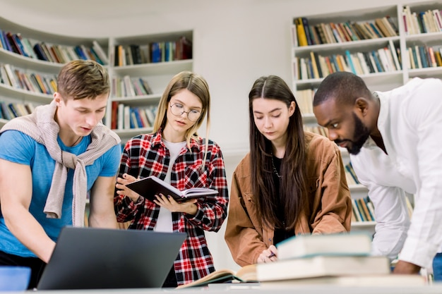 Beautiful young people in casual clothes, students, friends, working together in modern library