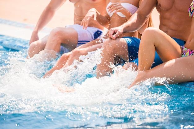 Beautiful young people having fun in swimming pool.