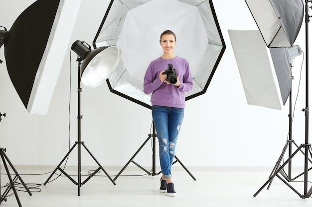 Красивый молодой фотограф с камерой в профессиональной студии