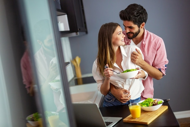 Beautiful young playful couple eating salad together at kitchen