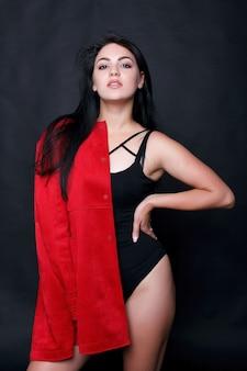 검은 배경에 서있는 블랙 바디에 아름 다운 젊은 통 통 여자. 플러스 사이즈 란제리의 섹시한 패션 모델, 검은 스튜디오 배경의 뚱뚱한 여성, 과체중 여성의 몸, 전체 길이 초상화