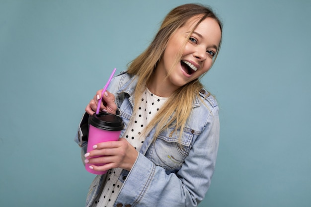 Beautiful young positive blonde woman wearing casual stylish clothes isolated over colorful background wall holding paper cup for mockup drinking coffee looking at camera