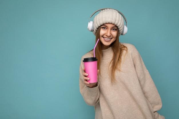 Красивая молодая позитивная блондинка в повседневной стильной одежде, изолированная на стене красочного фона, держит бумажный стаканчик для макета, пьющего кофе, глядя в камеру