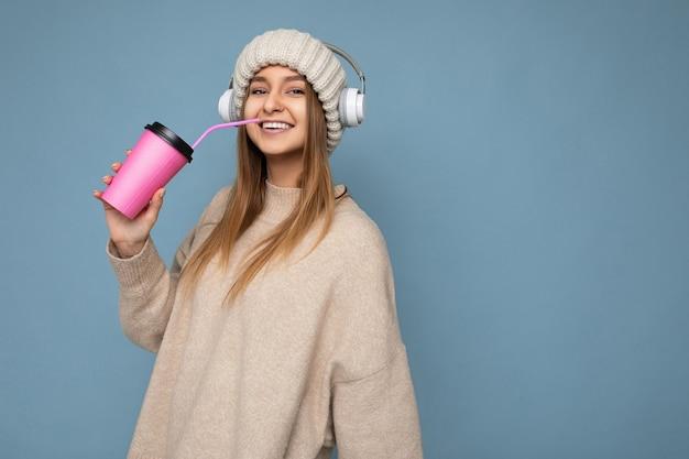 커피를 마시는 종이 컵을 들고 화려한 벽 벽에 고립 된 캐주얼 세련 된 옷을 입고 아름 다운 젊은 긍정적 인 금발 여자. 복사 공간