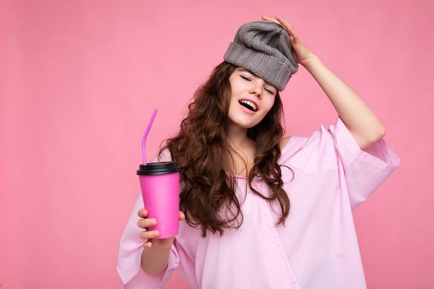 분홍색 셔츠와 회색 모자를 입고 아름 다운 젊은 긍정적 인 갈색 곱슬 여자