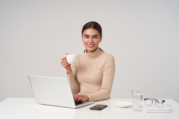 매력적인 미소로 유쾌하게보고 현대 노트북과 함께 테이블에 앉아 커피 한잔 마시고 공식적인 옷을 입고 아름다운 젊은 긍정적 인 어두운 머리 아가씨