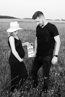 아름다운 젊은 임신한 부부는 해질녘 여름 저녁 들판을 걷고 태아의 초음파 사진을 봅니다. 흑백 사진. 아이를 기다리고 있습니다. 임신 관리.