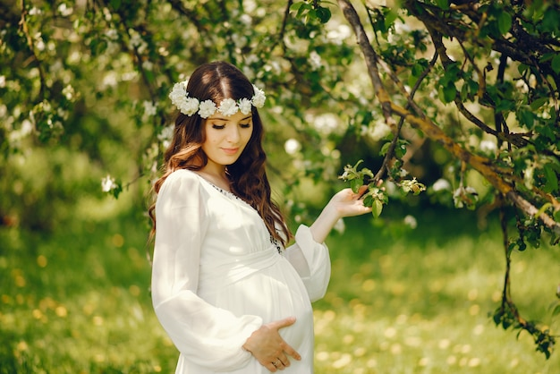 Красивая молодая беременная девушка в длинном белом платье и венок на голове