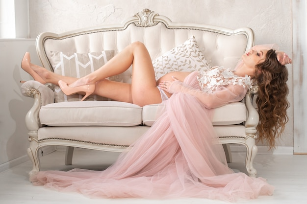 Beautiful young pregnant girl lies on a gorgeous couch