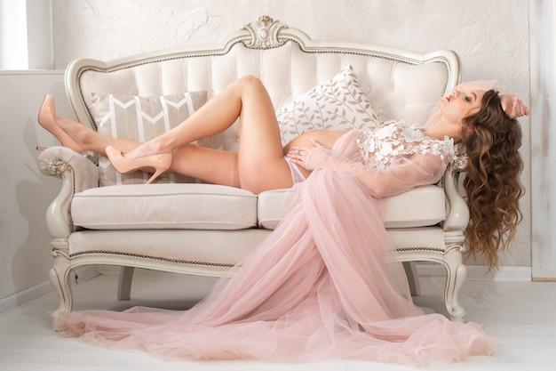 Красивая молодая беременная девушка лежит на великолепном диване