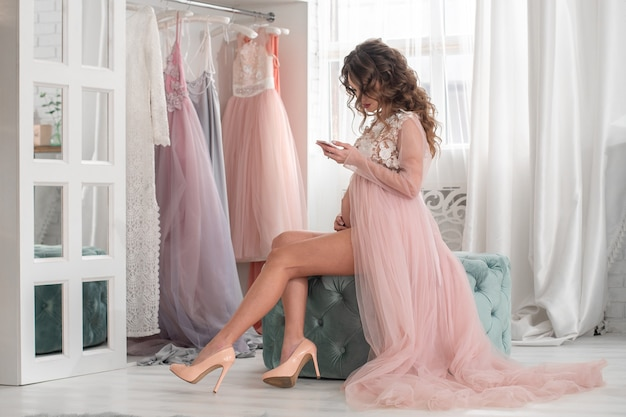 Beautiful young pregnant lady in a pink dress at home