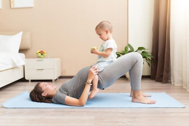 ヨガマットの上に横たわっている間笑顔の美しい若い妊婦と小さな男の子
