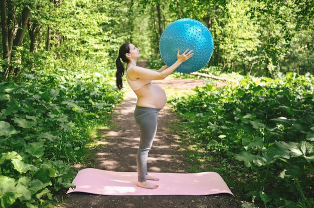 Beautiful young pregnant woman doing yoga exercising with fitness pilates ball in park outdoor