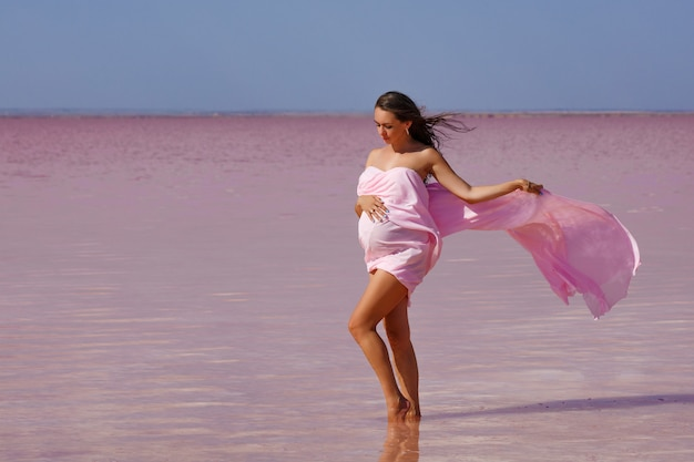 Beautiful young pregnant woman enjoying the sun on the beach, pink lake