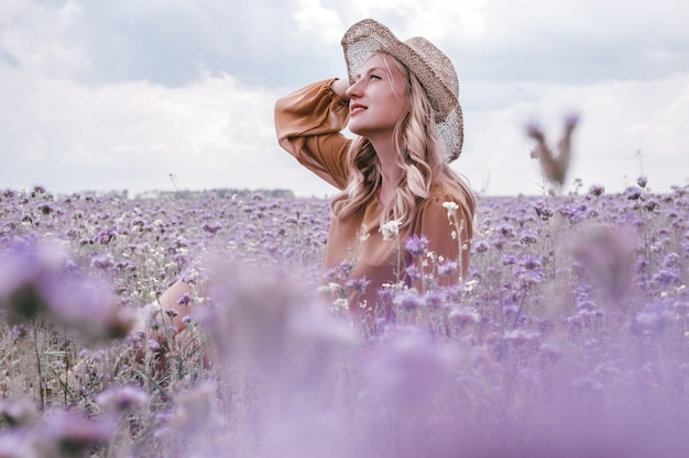 Beautiful young pregnant woman in hat in lavender field. blooming flowers
