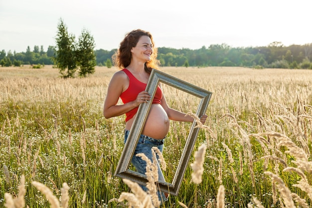 A beautiful young pregnant woman is holding the gold frame in the wheat field on a sunny day.