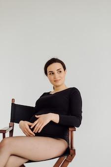 Красивая молодая беременная женщина позирует в студии в платье
