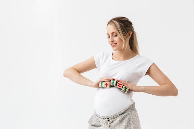 Красивая молодая беременная женщина, стоящая изолирована на белом фоне