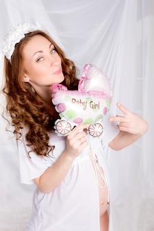Красивая молодая беременная женщина, подросток в белом нижнем белье с детским воздушным шаром